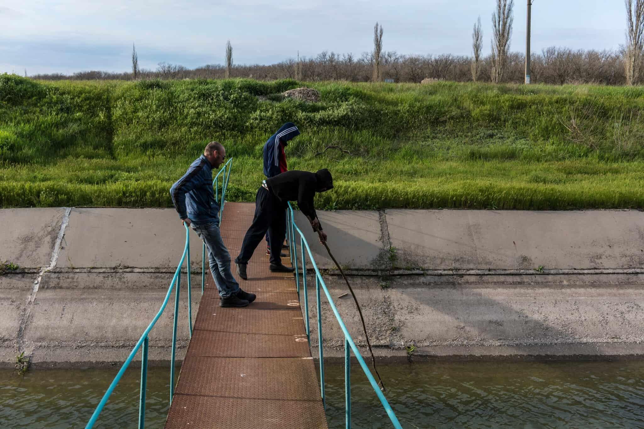 Местные жители ловят рыбу в канала в районе Каланчак.