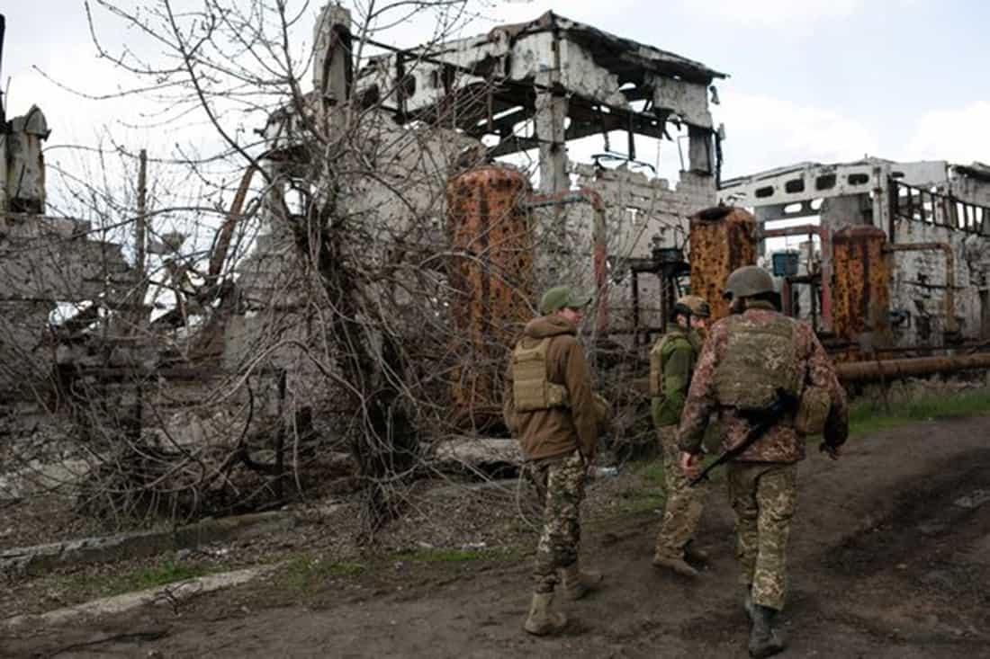 Солдаты проходят мимо зданий, сильно разрушенных в результате затяжного военного конфликта.